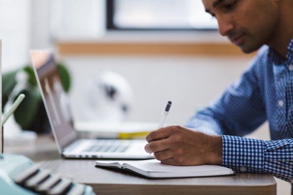 Mann sitzt mit Laptop und Notizbuch am Schreibtisch und symolisiert einen Auszubildenden